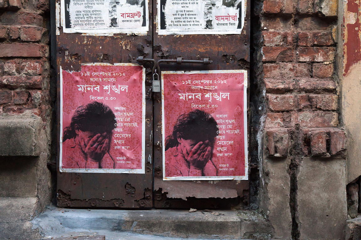 Poster showing a distressed woman, on a wall in Bowbazar, Kolkata, India.