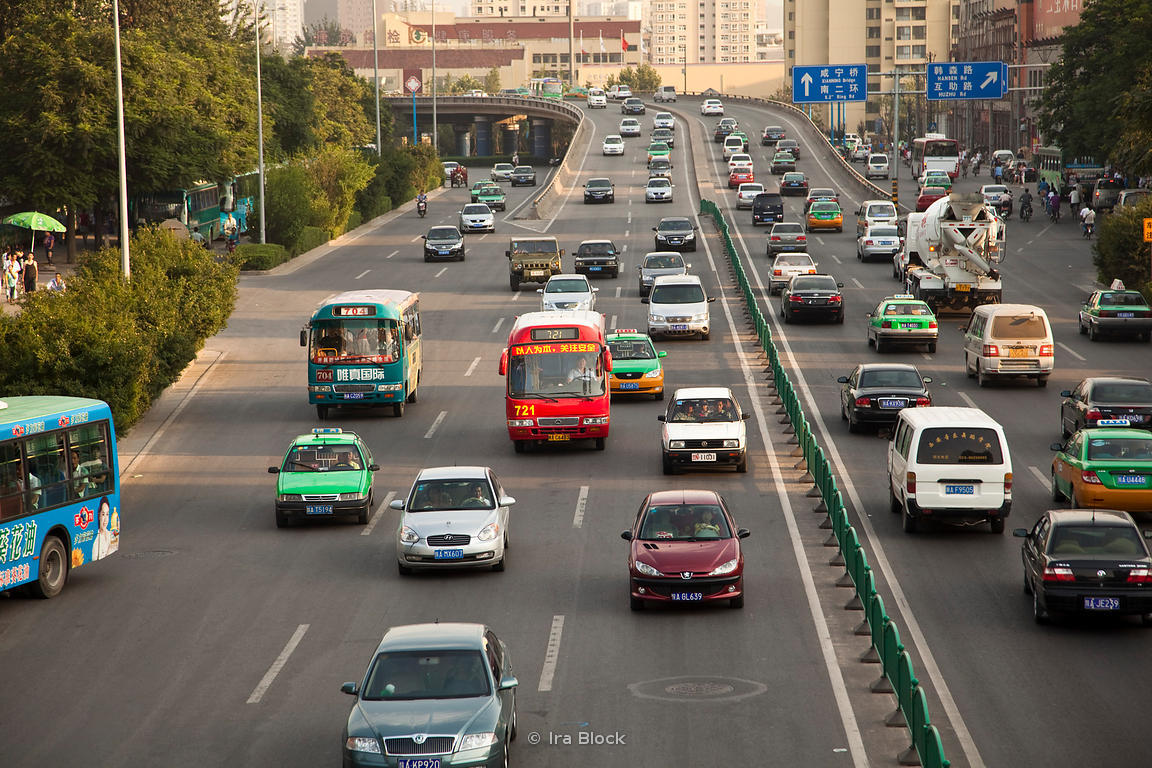 People commuting, through heavy traffic in both directions, on a highway in Xi'an.