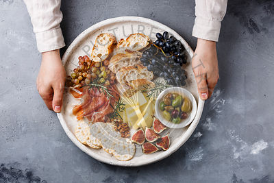 Italian snacks food with Ham, Olives, Cheese, Sun-dried tomatoes, Sausage and Bread in male hands on concrete background