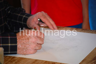Hands of an artist as he sketches a drawing