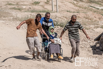 Three men help transport an old woman in a wheelchair on her way out of Mosul as they flee the conflict against ISIS. Mushaar...