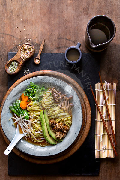 Vegan Japanese Ramen soup in grey bowl over wooden background with copy space