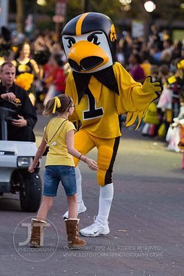 Herky the Hawk and a parade spectator dance on Clinton St during  the  University of Iowa homecoming Parade in Iowa City on F...