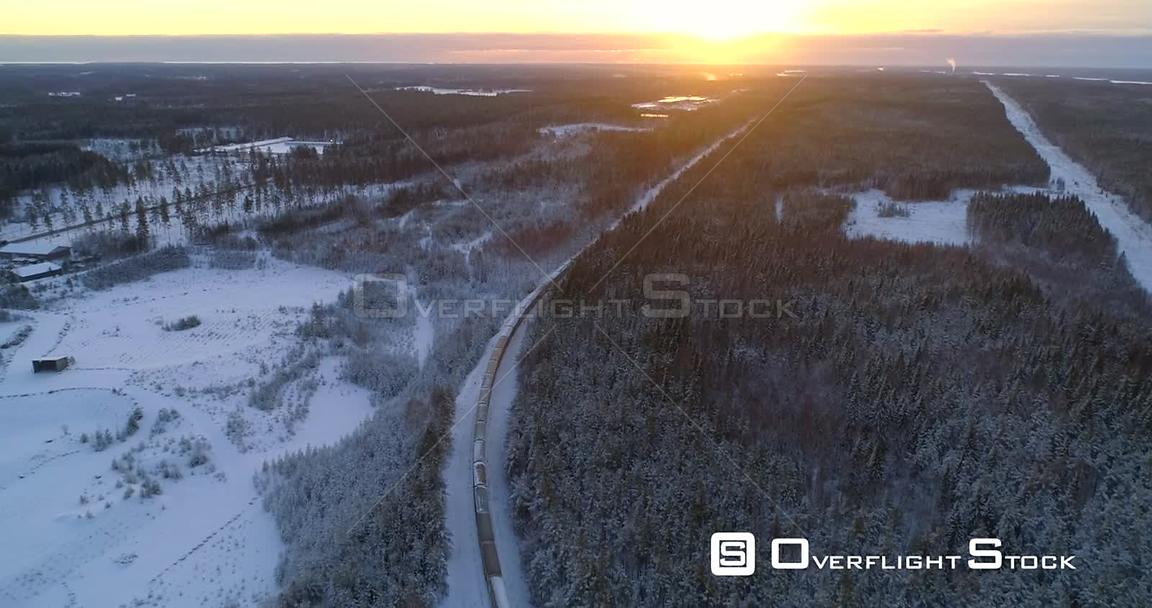 Train in Finnish Winter, Aerial, Tracking, Drone Shot, Following a Cargo Locomotive, in a Snowy Forest, Towards the Scandinav...