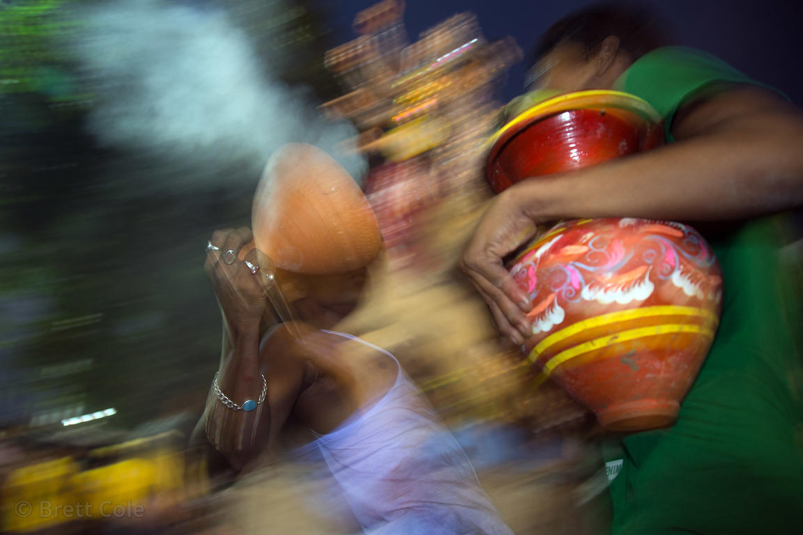 A family offers prayer in the form of dancing with smoking ghatam clay pots during the Durga Puja festival, Babughat, Kolkata...