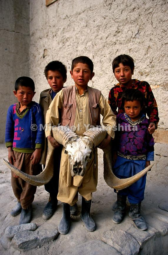 A group of children display the skull of an Ovis poli (Polo's Sheep).