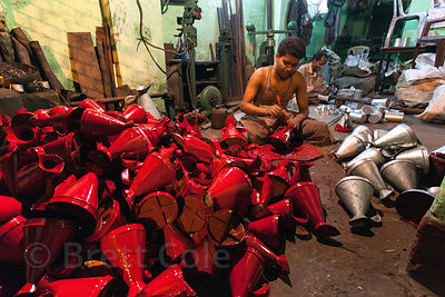 A man paints metal decanters at a small workshop in Sovabazar, Kolkata, India.