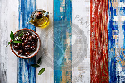Kalamata olives and Olive oil on wooden background copy space