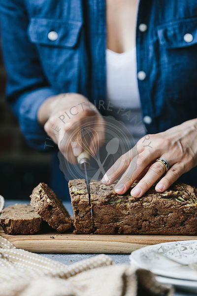 A woman is slicing a loaf of vegan zucchini and walnut bread.