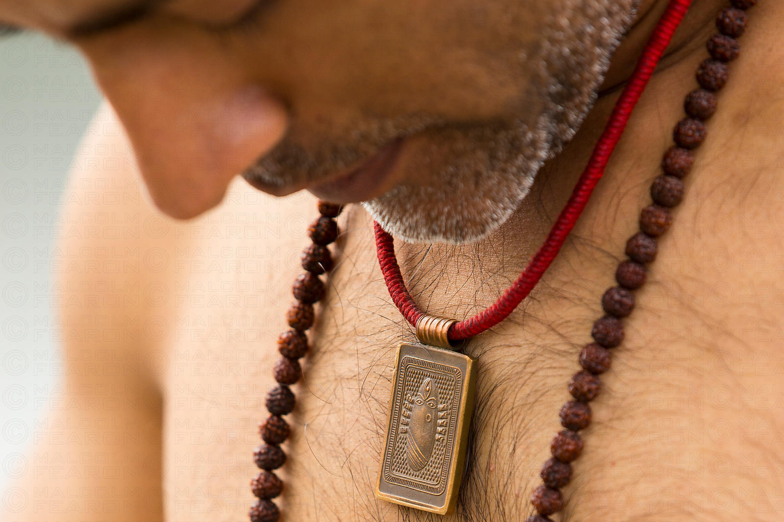 solo man wearing beads and neck pendant with head bowed