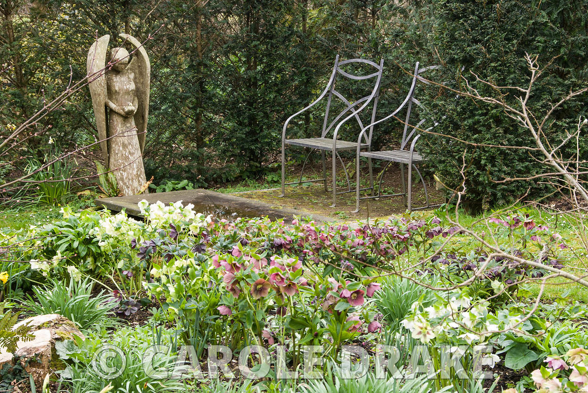 Angel carved by John Aulman from yew wood stands over a fountain of slate and granite made by Matt Robinson, seen across a be...