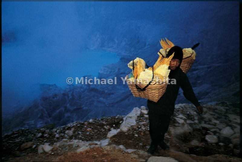 A sulfur collector carries the yellow blocks in cane baskets up the edge of the volcano in the early dawn haze.