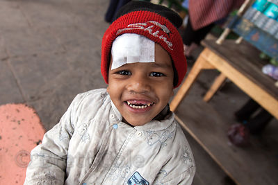 A boy with a bandaged forehead smiles at a free health clinic run by the French NGO Agir pour Benares, at the Burning Ghats i...