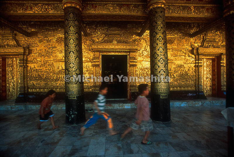 Taking their surroundings in stride, local boys flash past the gold walls of Wat Mai, an 18th-century temple adorned with sce...