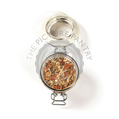 Homemade oatmeal granola with fruits and nuts in a glass jar on white background
