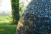 Dome structure made from thousands of bottles, with countryside beyond. Westonbury Mill Water Garden, Pembridge, Herefordshir...