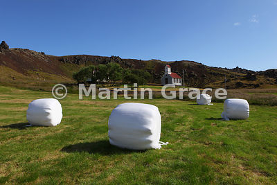 Mikholtskirkja (church), Southern Snaefellsnes, behind the plastic-wrapped haylage bales that typify the landscape in July
