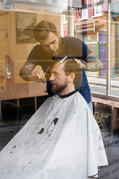 UK - London - A fashionable man has a haircut in a barber shop on Brick Lane