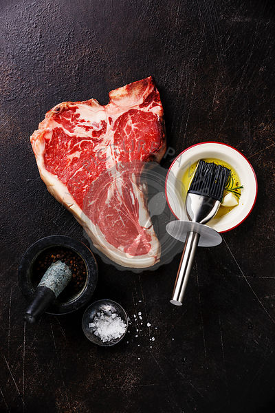 Raw fresh meat Dry Aging Steak T-bone and seasoning on dark background