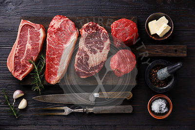 Variety of Raw Black Angus Prime meat steaks Blade on bone, Striploin, Rib eye, Tenderloin fillet mignon on wooden board and ...