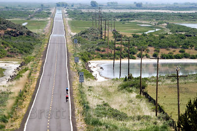 Bicyclists travel in Summer heat down Highway 161 near the Lower Klamath NWR, California