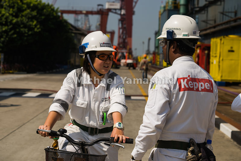Two Keppel FELS employees pause for a quick exchange amid a sunny afternoon at the yard.