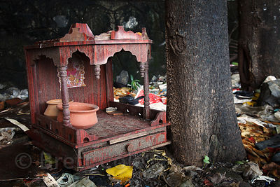 A small wooden Hindu altar sits on a garbage pile in the Dharavi slum, Mumbai, India.