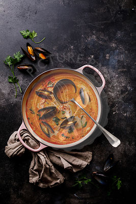Seafood soup with prawns, mussels and tomato on dark background copy space