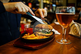 Burger with French fries and Beer, fork and knife in male hands on wooden table background
