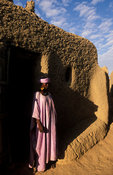 Peul (or Fula) woman in the entrance of her traditional mud house in a Peul village near Djenné, Mali