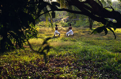 India - Kerala - A dusk, two students practise dance moves in the grounds of the Kerala Kalamandalam