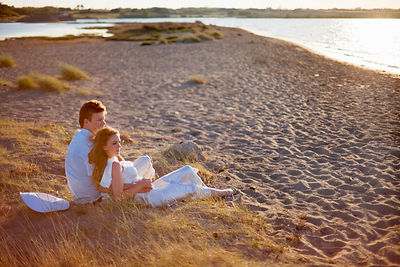 Newlywed couple sitting on beach