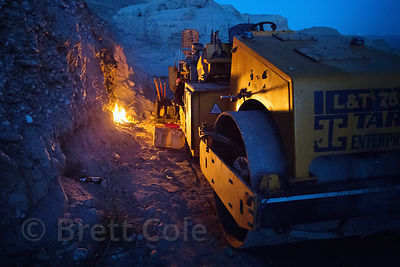 Fire next to a road grader at a construction site in Leh, Ladakh, India. There are four people sleeping under the machine.