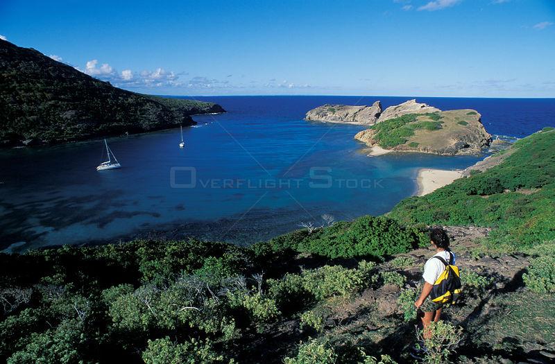 Woman looking over a bay with moored cruising yachts on 'Les Saintes' island, Caribbean.