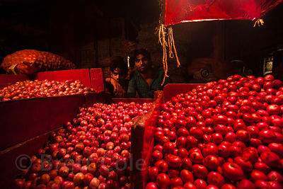 Onions for sale under red lights at the Kole wholesale vegetable market, Bowbazar, Kolkata, India. Kole is one of the largest...