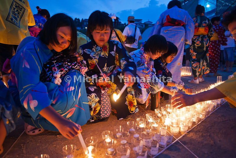 10,000 candle ceremony organized by Kobe Junior Chamber of Commerce as part of Obon celebration. Candles form the character f...