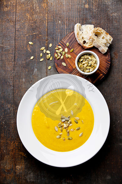 Pumpkin soup in white plate on wooden background