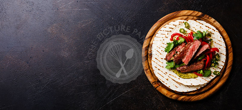 Grilled Beef steak Fajitas taco tortillas with green salsa and bell pepper on dark background copy space