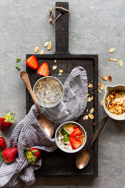 Chia pudding with strawberries, almonds and mint on black wooden board over grey concrete background