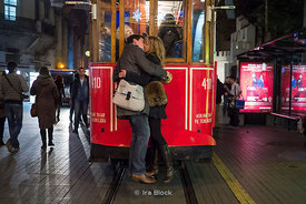 A couple kissing in front of the Istiklal Street trolley that travels between Taksim Square and the Tünel in Istanbul.
