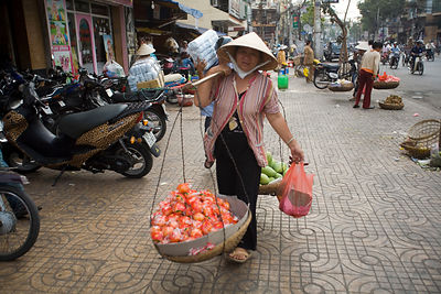 A woman carries a basket of fruit