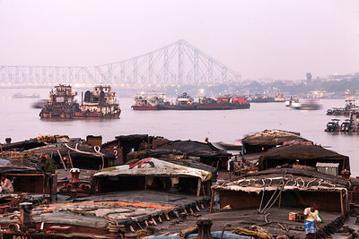 View of ships on the Hooghly River and Howrah Bridge, Kolkata, India.