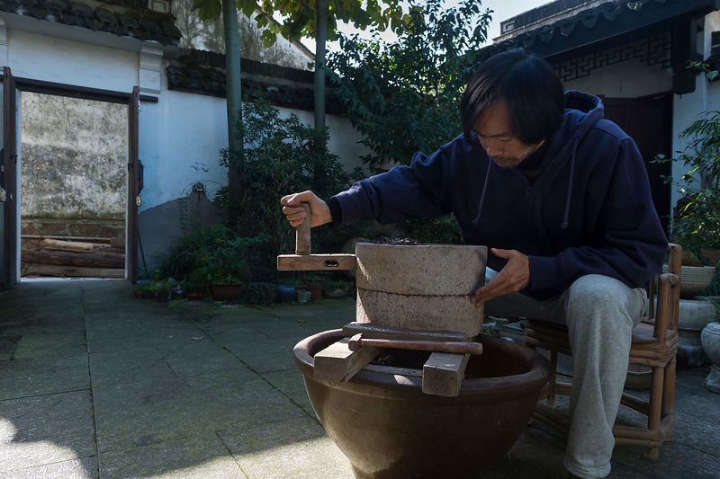 Wu Zhi Qiang, 50, master potter, tea grower and clay expert, hand-grinding Yixing purple clay in courtyard of his house, Shao...