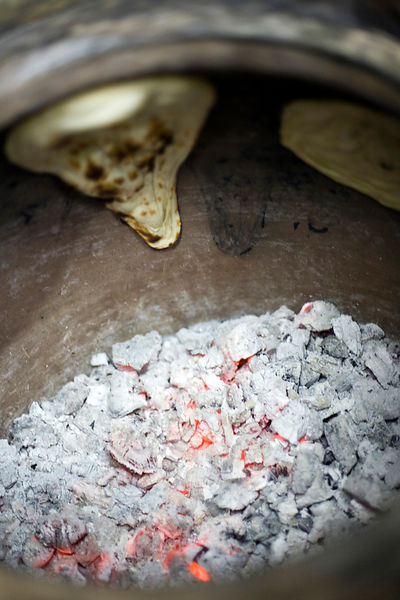 India - Delhi - Naan bread in the tandoor oven at the Village Restaurant in Siri Fort