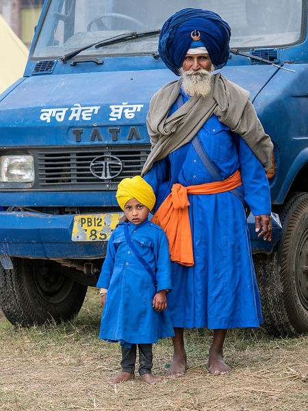 An old nihang poses with his grandson for the camera during the Holla mohalla festival.