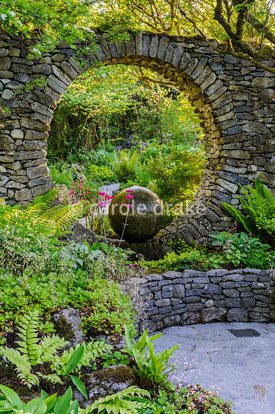 A Moon Window, a circular opening in a stone wall, frames a cast concrete water feature, surrounded by shade planting includi...