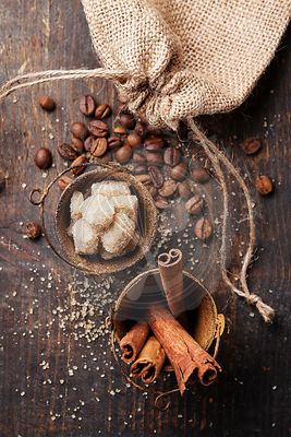 Cinnamon sticks, cane sugar and coffee beans on wooden background