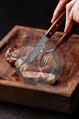 Sliced grilled meat steak New York Striploin with knife and fork in male hands on wooden board on black background close-up
