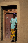 Woman stading in a traditional Moroccan style door, Djenné, Mali