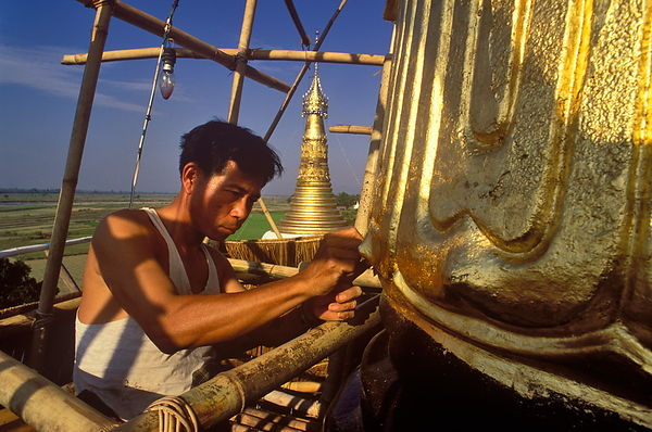 Man gilding spire of stupa
